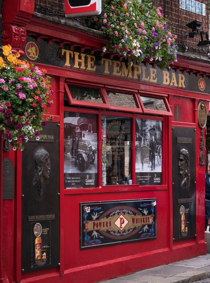 五颜六色的爱尔兰客栈外部在有外面花的坦普尔酒吧区都伯林 免版税库存图片