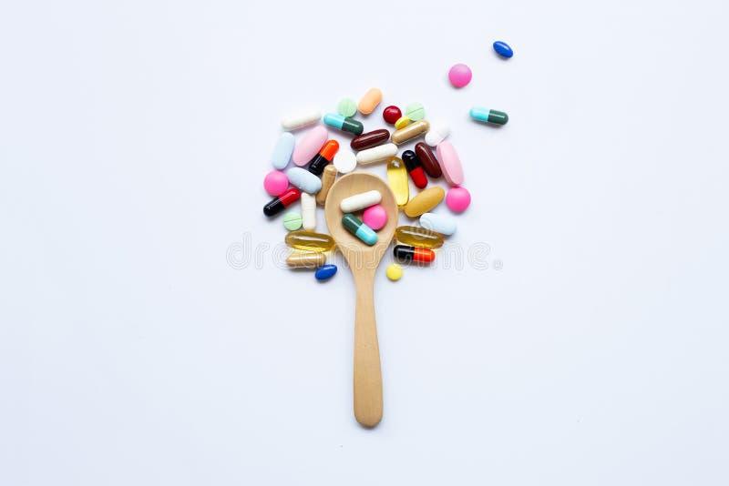 五颜六色的片剂、胶囊和药片与木匙子在白色 库存照片