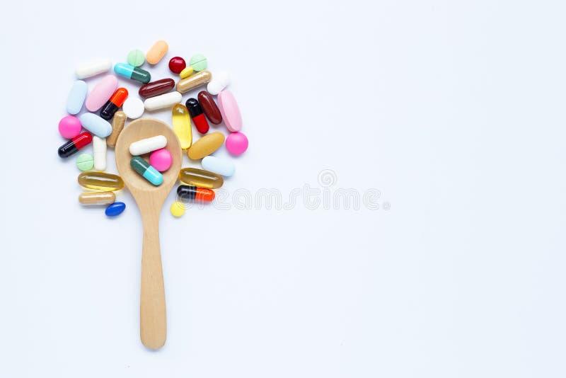 五颜六色的片剂、胶囊和药片与木匙子在白色 图库摄影