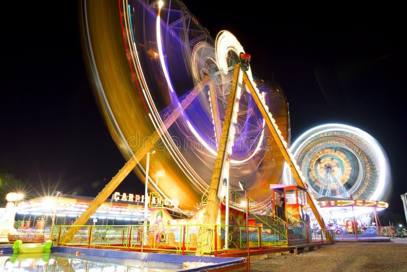 五颜六色的狂欢节转动在行动的弗累斯大转轮和长平底船被弄脏在晚上 免版税库存图片