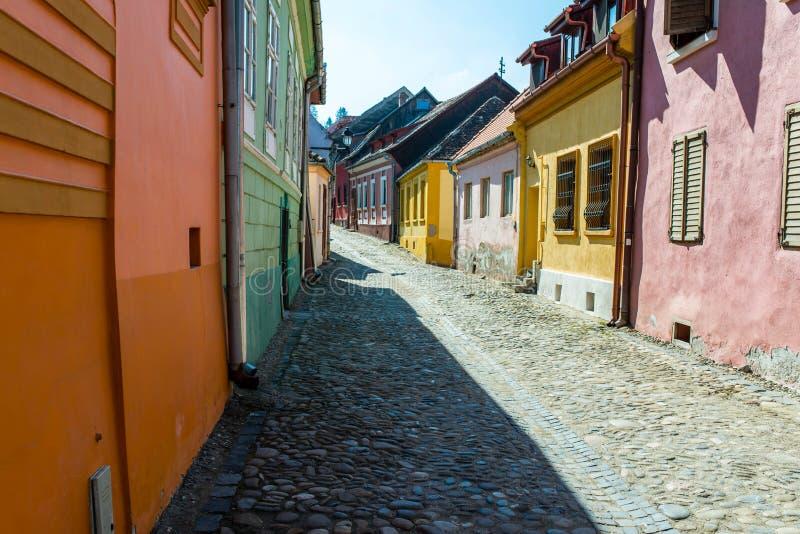 五颜六色的狭窄的中世纪街道在一个明亮的春日在锡吉什瓦拉 库存照片
