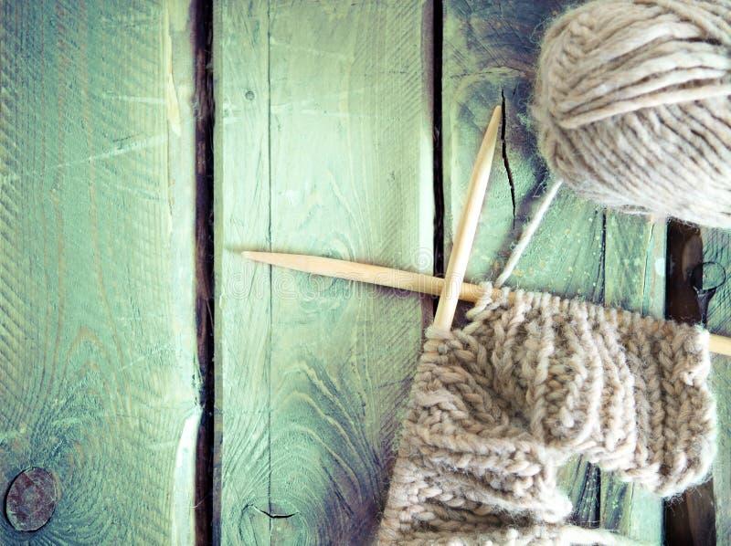 五颜六色的球毛线和编织在一张木桌上 免版税库存照片