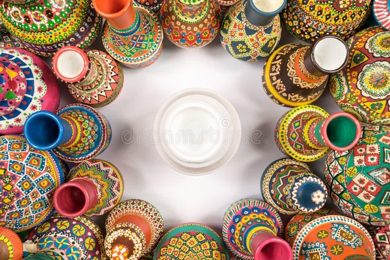 五颜六色的瓦器花瓶在唯一白色花瓶附近变紧密 免版税库存图片