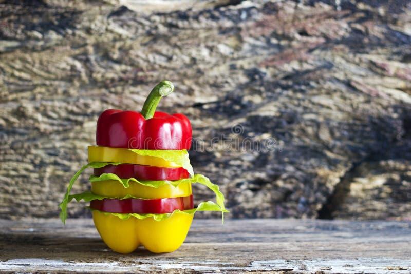 五颜六色的甜椒切在木背景的装饰 免版税图库摄影