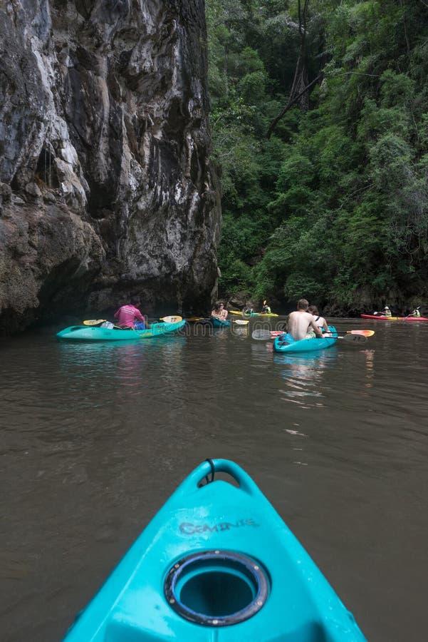 五颜六色的皮船的游人在峭壁和密林下 库存图片