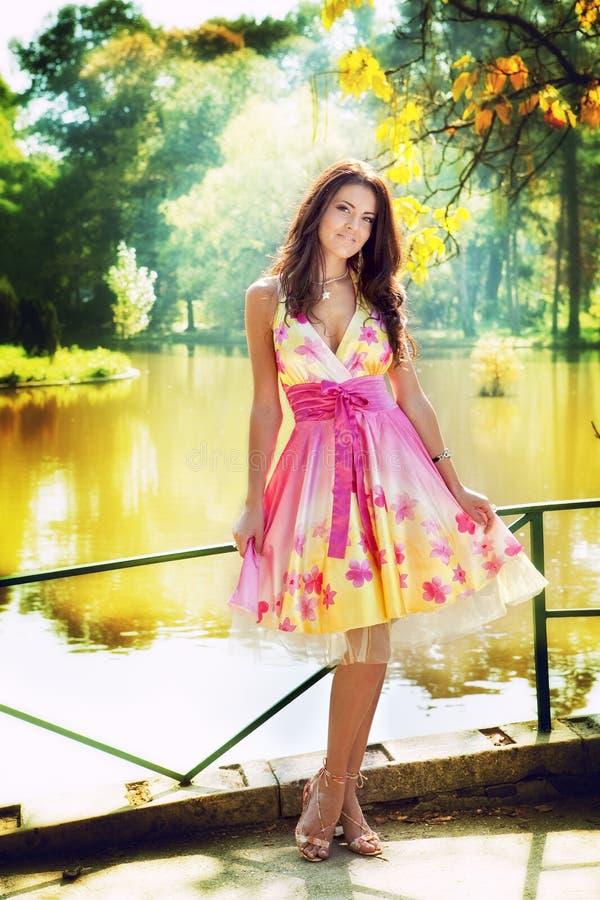 五颜六色的礼服室外性感的妇女 免版税库存图片