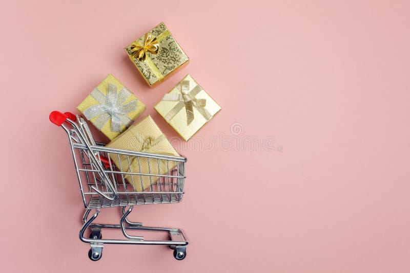 五颜六色的礼物盒,超级市场在桃红色背景的购物车 免版税库存照片