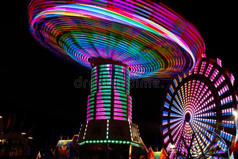 五颜六色的空转的摇摆,弗累斯大转轮在晚上 免版税库存图片