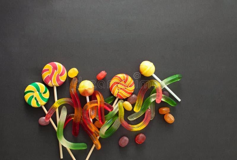 五颜六色的糖果为在黑背景的万圣夜 库存图片