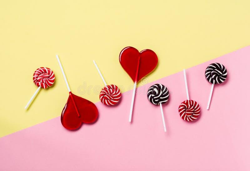 五颜六色的糖果和棒棒糖在淡黄色背景 免版税库存图片