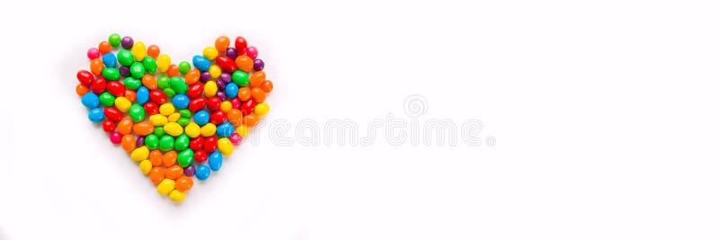 五颜六色的糖果安排了作为在白色背景的心脏 库存照片