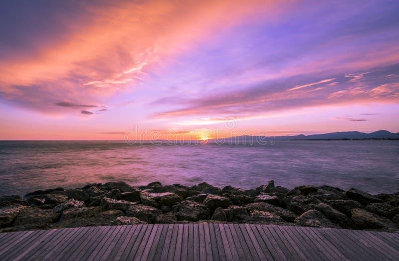 五颜六色的紫外黑暗的日落在海和与一个木走道和岩石在前景 免版税图库摄影