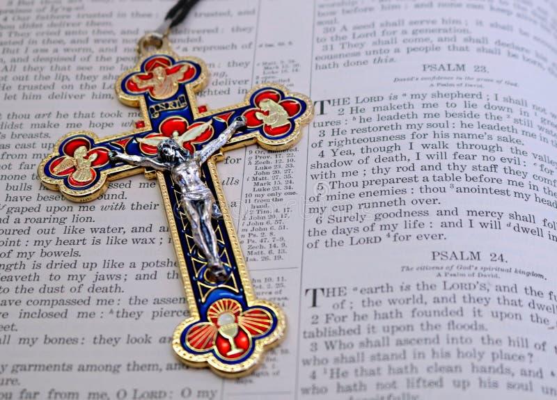 五颜六色的红色蓝色金子和银色耶稣受难象在第23首赞美诗旁边 免版税库存照片