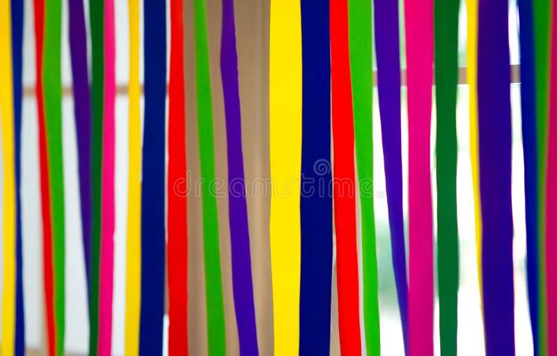 五颜六色的纸条纹在与自然光backgr的窗口垂悬 库存图片