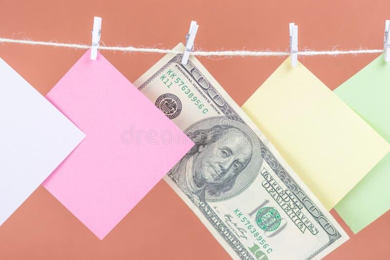 五颜六色的纸牌和在棕色背景隔绝的金钱垂悬的绳索 库存图片