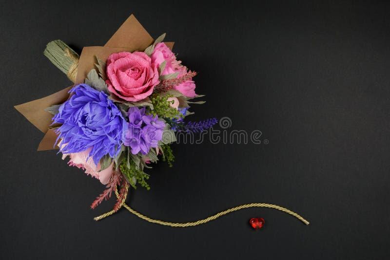 五颜六色的纸花花束和在黑背景的小红色心脏作为明信片的的邀请信一个背景 免版税库存照片