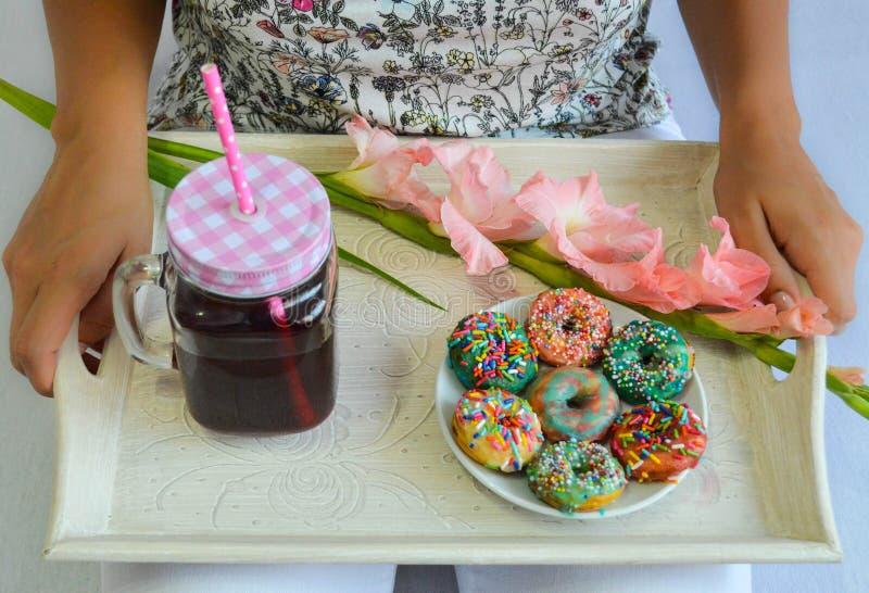 五颜六色的美国油炸圈饼和新鲜的樱桃汁服务早餐 免版税图库摄影