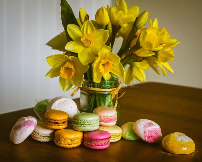五颜六色的自创Macarons和蛋白甜饼在厨房用桌上与黄水仙 库存图片