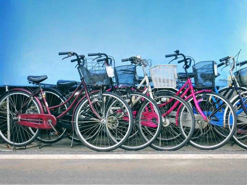 五颜六色的自行车行有路停放的前面篮子的对蓝色墙壁 免版税库存图片