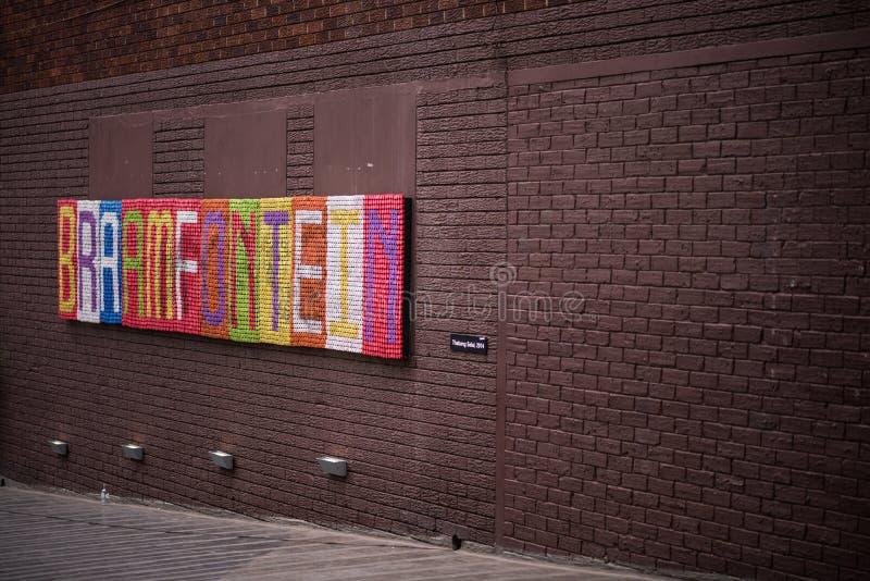 五颜六色的艺术性的Braamfontein标志由瓶上面做成,在一块棕色被绘的砖 库存图片