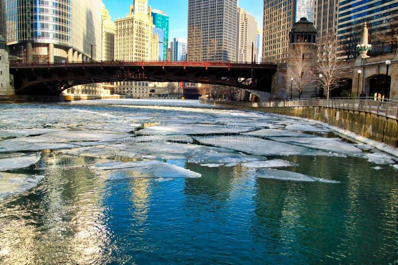 五颜六色的芝加哥都市风景的反射在冻芝加哥河的有漂浮在桥梁下的冰大块的 免版税图库摄影