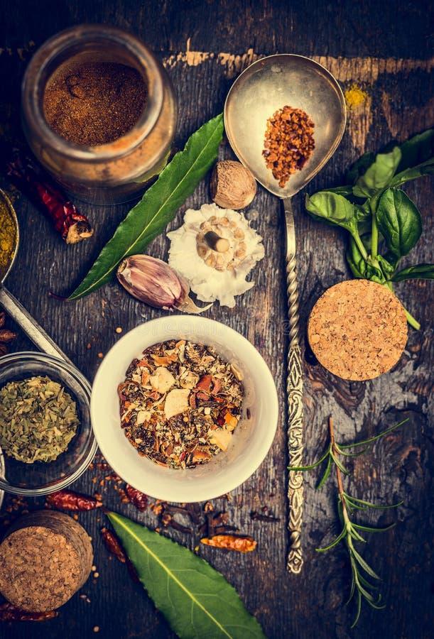 五颜六色的草本和香料的选择在匙子和碗在土气木背景 库存图片