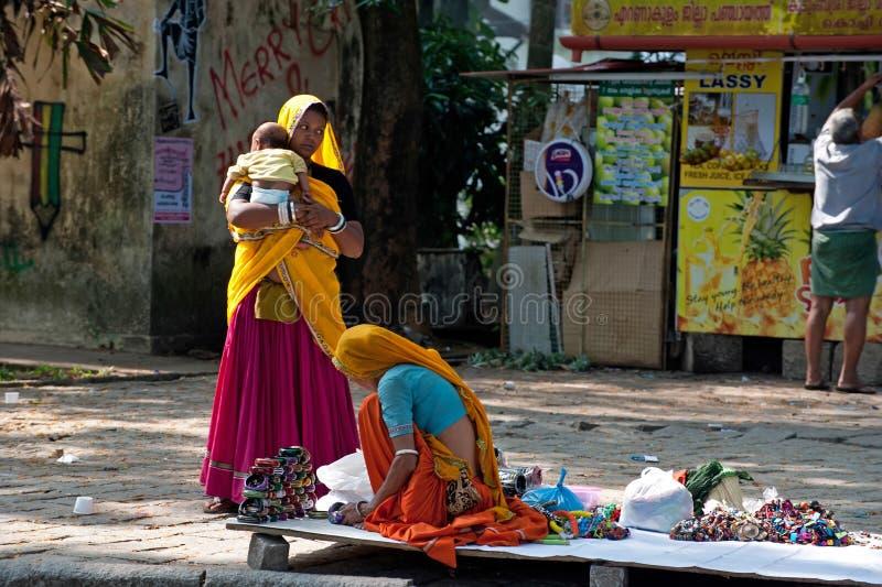 五颜六色的莎丽服的印地安妇女卖纪念品、手镯和便宜的首饰 图库摄影