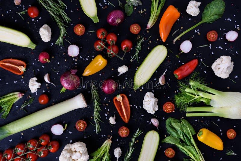 五颜六色的菜和香料在黑背景 产物显示 有机健康素食食物 农夫市场布局 顶层 免版税库存图片