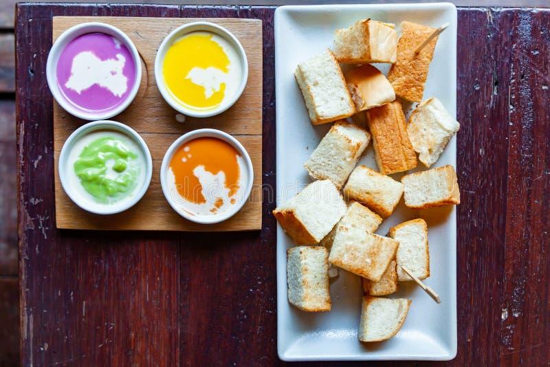 五颜六色的蒸的乳蛋糕和牛奶用蒸的面包在Whi 库存图片