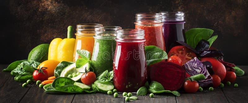 五颜六色的蔬菜汁和圆滑的人从蕃茄,红萝卜,胡椒,圆白菜,菠菜,甜菜根在瓶在厨房用桌,素食主义者上 库存图片