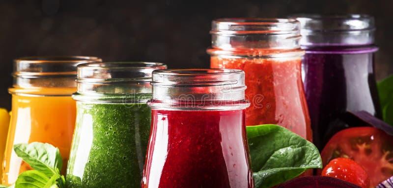 五颜六色的蔬菜汁和圆滑的人从蕃茄,红萝卜,胡椒,圆白菜,菠菜,甜菜根在瓶在厨房用桌,素食主义者上 库存照片