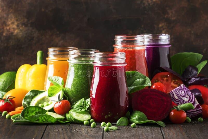 五颜六色的蔬菜汁和圆滑的人从蕃茄,红萝卜,胡椒,圆白菜,菠菜,甜菜根在瓶在厨房用桌,素食主义者上 免版税图库摄影