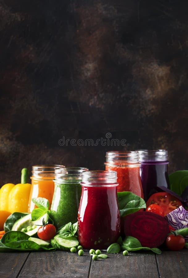 五颜六色的蔬菜汁和圆滑的人从蕃茄,红萝卜,胡椒,圆白菜,菠菜,甜菜根在瓶在厨房用桌,素食主义者上 免版税库存图片