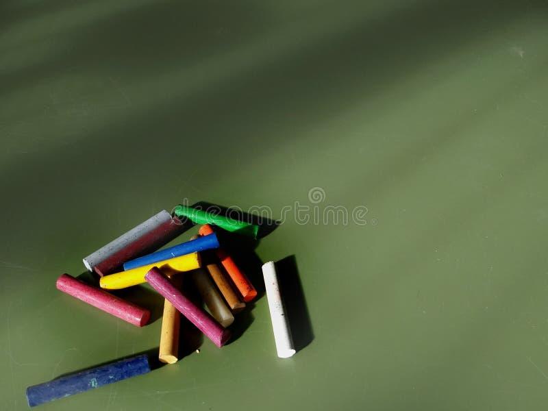 五颜六色的蜡笔,在板隔绝的油柔和的淡色彩,葡萄酒守旧派作用-写的背景 免版税图库摄影