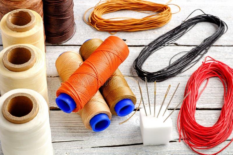 五颜六色的蜡绳子,皮革螺纹在白色木背景皮革制作的,柳条工作的和手工造 库存图片