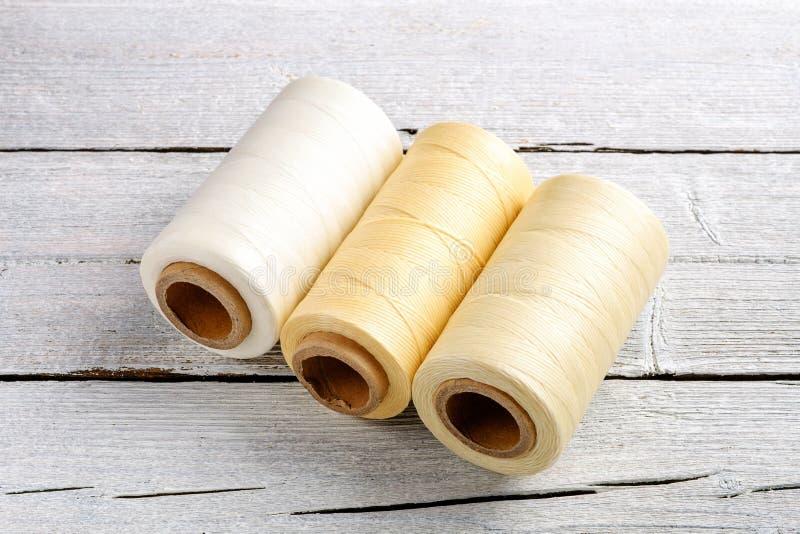 五颜六色的蜡绳子,皮革螺纹在白色木背景皮革制作的,柳条工作的和手工造 免版税图库摄影