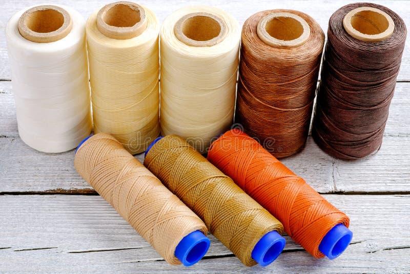 五颜六色的蜡绳子,皮革螺纹在白色木背景皮革制作的,柳条工作的和手工造 图库摄影
