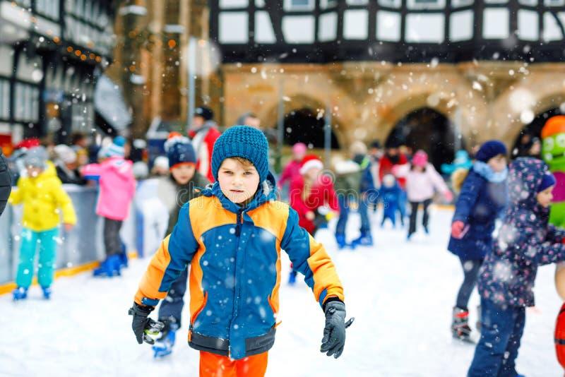 五颜六色的衣服暖和的愉快的小孩男孩滑冰在圣诞节市场或市场溜冰场的  获得健康的孩子乐趣  库存照片