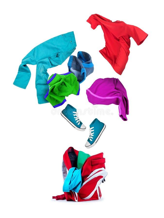 五颜六色的衣物落入在白色隔绝的背包 库存照片