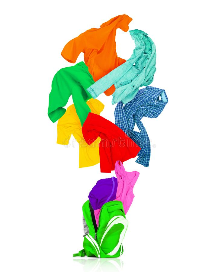 五颜六色的衣裳飞行在白色隔绝的一个绿色背包外面 免版税库存图片