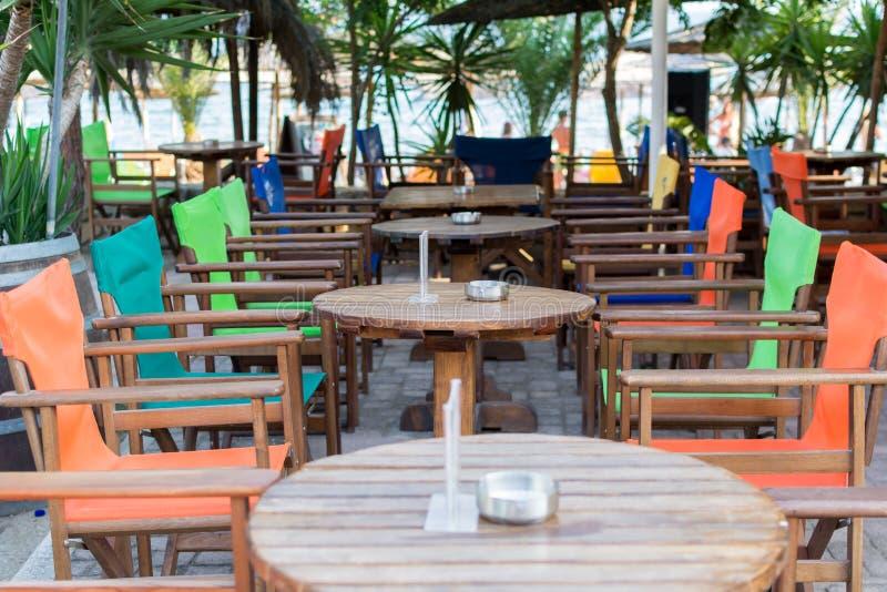 五颜六色的表和椅子在海滩在海附近禁止餐馆, 免版税库存图片