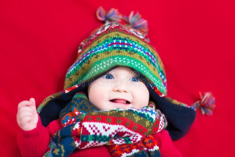 五颜六色的被编织的帽子和围巾的滑稽的女婴 库存照片