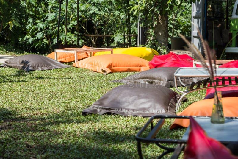 五颜六色的装豆子小布袋椅子和短的桌野餐的 图库摄影