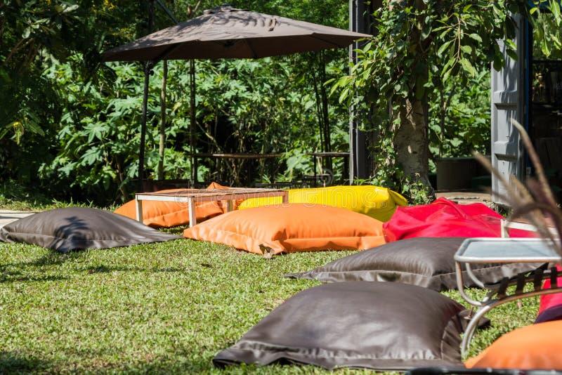 五颜六色的装豆子小布袋椅子和短的桌野餐的 库存图片