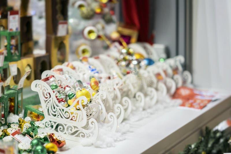 五颜六色的装饰品、圣诞节球和白色木爬犁 圣诞节装饰销售  被弄脏的抽象光 图库摄影