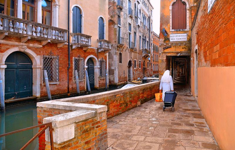 五颜六色的角落和老大厦和建筑学与水运河和尼姑尽头的在威尼斯,意大利 库存照片