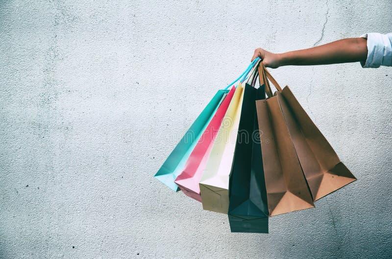 五颜六色的购物袋由夫人手举行的特写镜头,在难看的东西wal表面的水泥前面 免版税库存照片