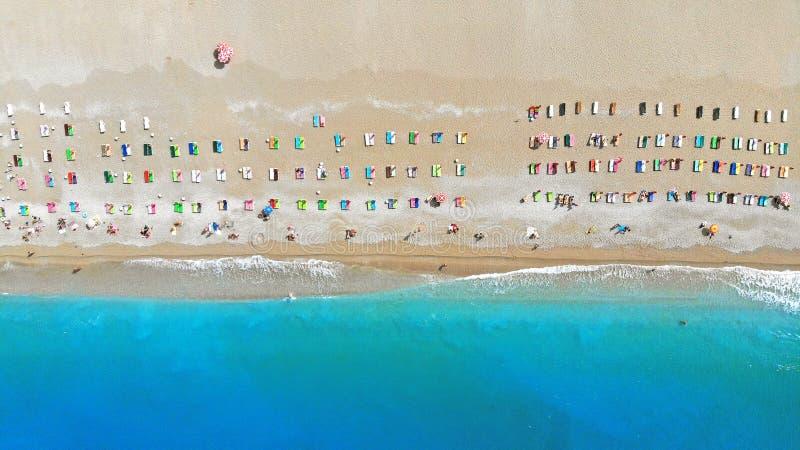 五颜六色的轻便马车休息室轻便折叠躺椅鸟瞰图在海滩的绿松石海 波浪洗涤岸 免版税图库摄影