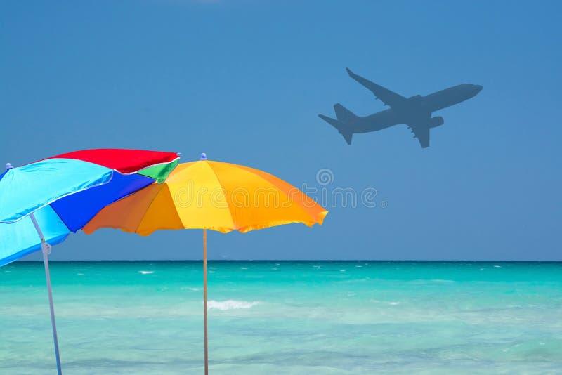 五颜六色的遮阳伞和飞机绿松石水 免版税库存照片