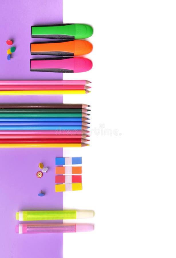 五颜六色的铅笔和霓虹笔在淡紫色纸和白色 库存照片